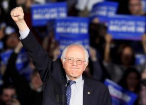U.S. Democratic presidential candidate Bernie Sanders raises a fist as he speaks at his caucus night rally Des Moines