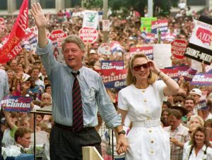 ST. LOUIS, UNITED STATES: Democratic presidential candidate Bill Clinton (L) waves to supporters as he holds the hand of his wife Hillary, 22 July, 1992 after speaking at a rally. St. Louis was the last stop on the Clinton-Gore campaign's bus tour. The crowd was estimated at 40,000. (Photo credit should read TIM CLARY/AFP/Getty Images)